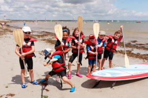 groupe d'enfants sur la plage de Langoz, équipés de gilets de sauvetage et de pagaies