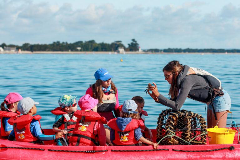 monitrice de voile montrant un petit crabe à des jeunes enfants