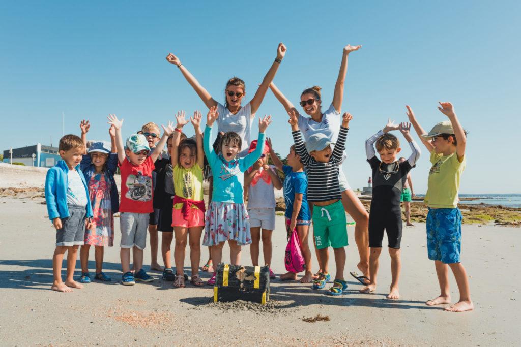 groupes d'enfants sur la plage avec deux moniteurs de voiles, levant les bras au ciel en souriant