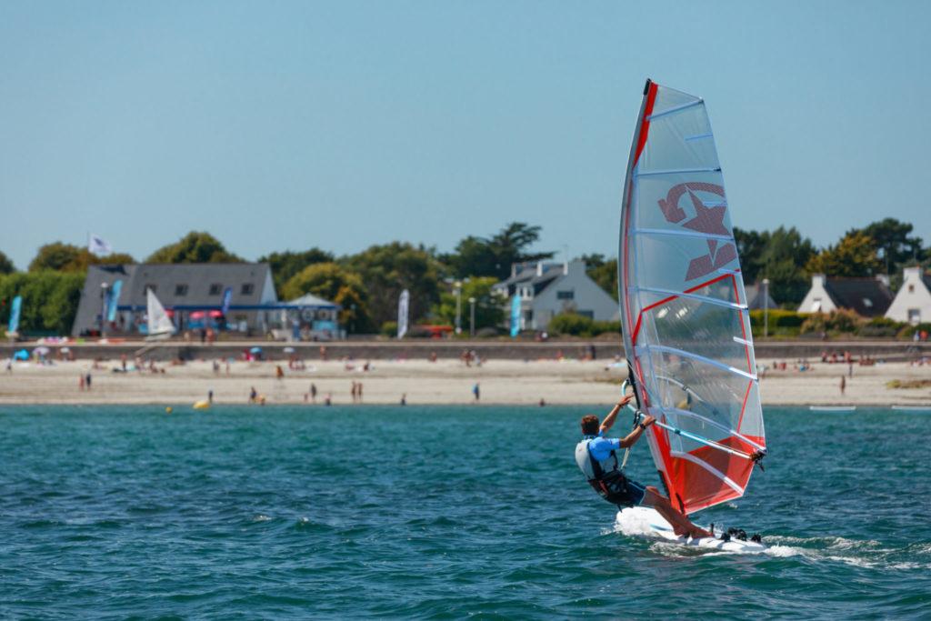 Planche à voile orange naviguant à Loctudy, avec la plage de Langoz en arrière plan
